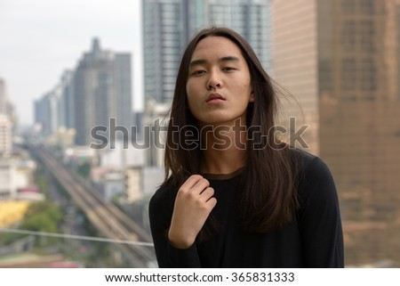 Asian man with long hair outdoors