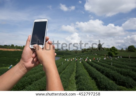Asian man with mobile phone shooting photo and operate mobile phone - stock photo