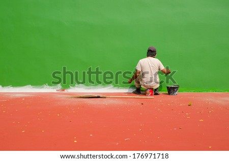 Asian man With Paintbrush and green blank wall