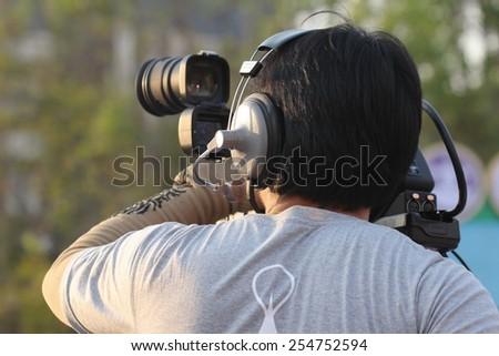 Asian man with video camera ,Video reporter, cameraman,  young videographer outdoor - stock photo
