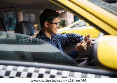 Asian man working as taxi driver in yellow car, with female client paying cash and leaving - stock photo