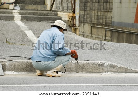 Asian man working on a sidewalk