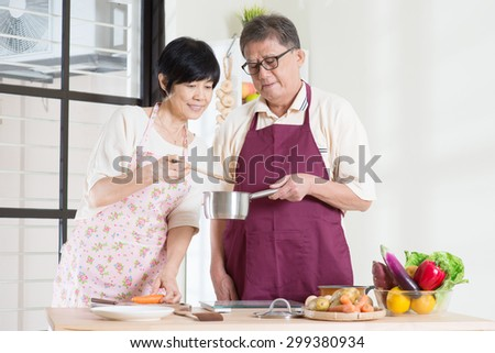 Asian mature couple cooking food at kitchen. Seniors living lifestyle at home. - stock photo