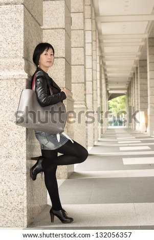 Asian mature woman at street, full length portrait.