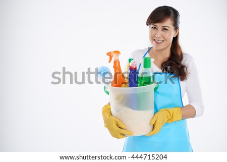 Asian mature woman holding a bucket with detergents and sprays