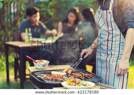 Asian men are cooking for a group of friends to eat barbecue