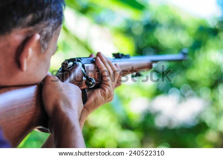Asian men holding a rifle. - stock photo