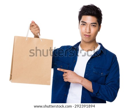 Asian mixed Indian man finger point to shopping bag - stock photo