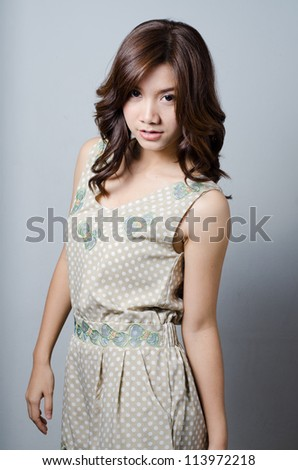 Asian model girl posing on gray background - stock photo
