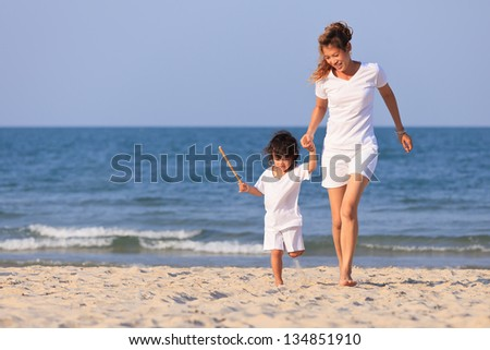 Asian mom and boy play on tropical beach - stock photo