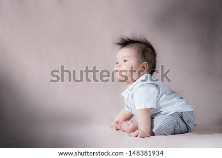 Asian 5 month old baby with wild scruffy hair making a funny face while looking up