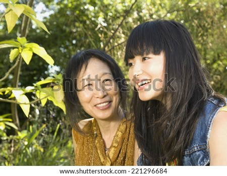 Asian mother and adult daughter outdoors - stock photo