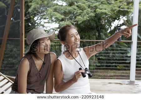 Asian mother and adult daughter pointing and looking - stock photo