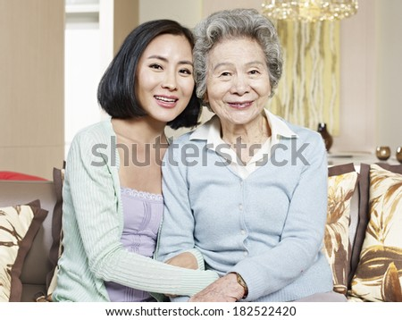 asian mother and adult daughter sitting on couch smiling - stock photo