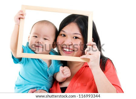 Asian mother and baby boy looking fun through an empty frame - stock photo