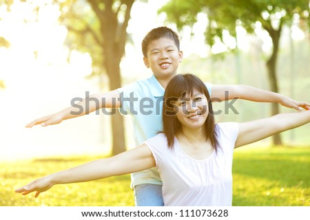 Asian mother and child happy playing on tropical park