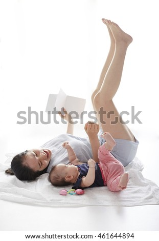 Asian mother and children, lying on the ground
