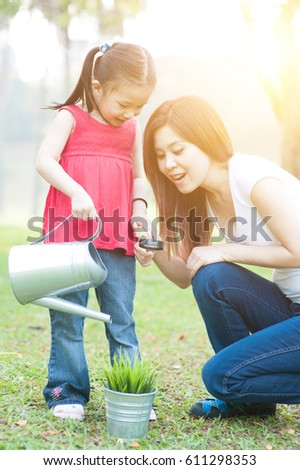 Asian mother and daughter are exploring nature and having fun. Family outdoor fun, morning with sun flare.