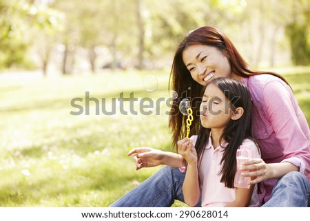 Asian mother and daughter blowing bubbles in park - stock photo