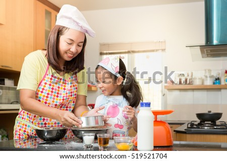 Asian mother and daughter enjoy making bakery cake, Little Asian girl and mom enjoy decorate cake in real life kitchen,Asian mom teaching daughter to learn making pancake in real life kitchen at home