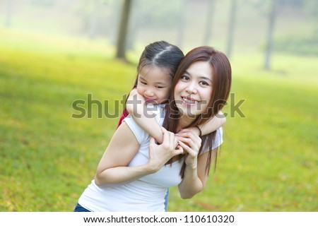 Asian mother and daughter having fun in park - stock photo