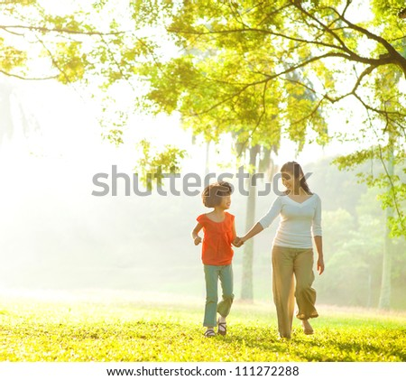 Asian mother and daughter holding hands walking at outdoor park - stock photo