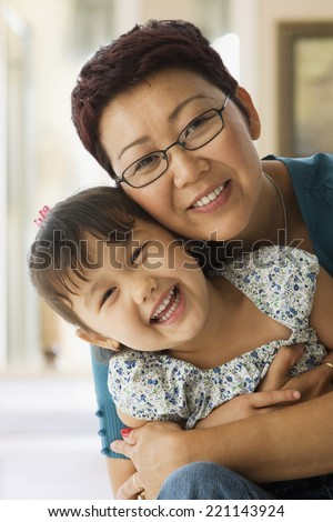 Asian mother and daughter hugging - stock photo