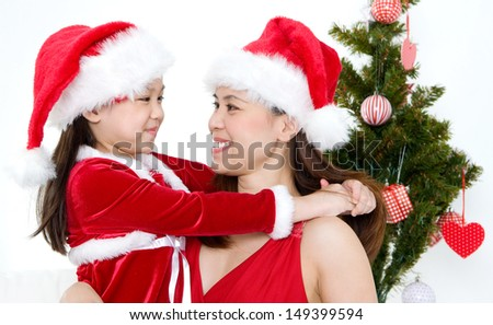 Asian mother and daughter in christmas outfits looking at each other - stock photo