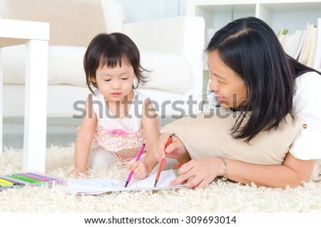 Asian mother and daughter lying on carpet and drawing on paper with colored pencil  - stock photo