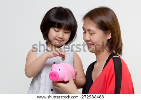 Asian Mother and daughter putting coins into piggy bank - stock photo
