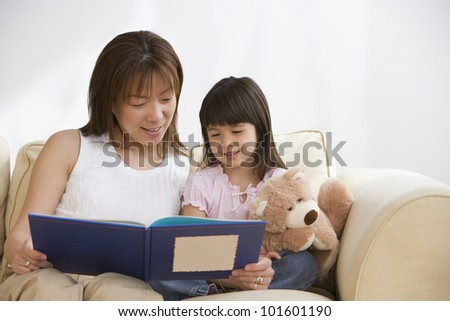 Asian mother and daughter reading - stock photo