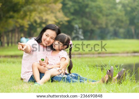 Asian mother and daughter sit in the garden - stock photo