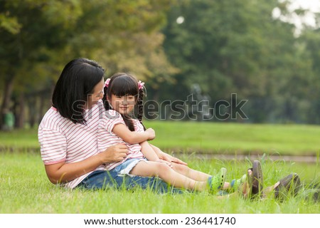 Asian mother and daughter sitting in the garden