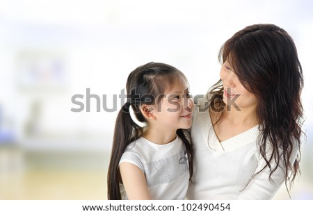 Asian mother and her daughter having conversation in home - stock photo