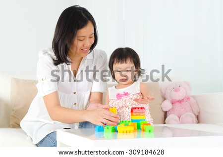 Asian mother and kid playing building block - stock photo