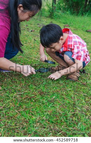 Asian mother and lovely son enjoying in nature. Young boy exploring nature at ground with magnifying glass. children playing outdoors in the day time and happy family concept. - stock photo