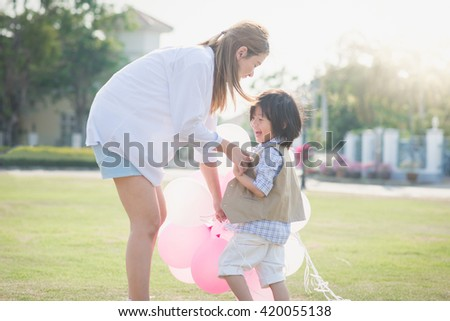 Asian mother and son holding hand together and walking in the park under sunlight - stock photo