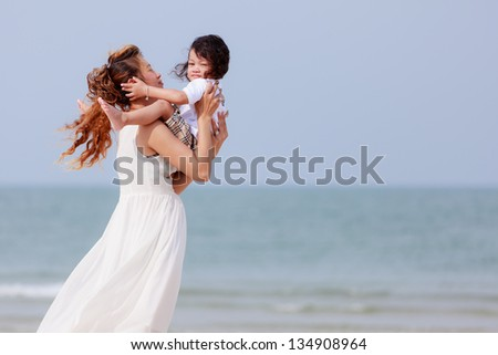 Asian mother and son playing on tropical beach