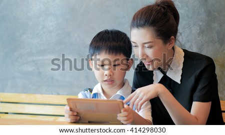Asian mother and son using tablet computer - stock photo