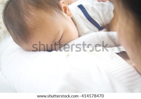 Asian mother breastfeeding her baby boy - stock photo