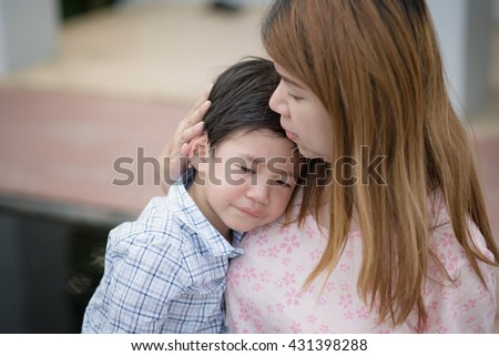 Asian mother embracing and consoling her son
