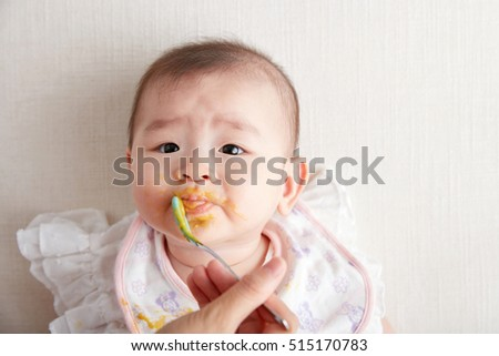 Asian Mother feeding daughter baby food
