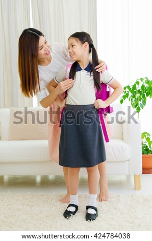 Asian mother get her daughter ready to school - stock photo