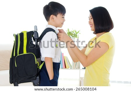 Asian mother get her son ready to school - stock photo
