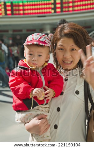 Asian mother holding baby - stock photo