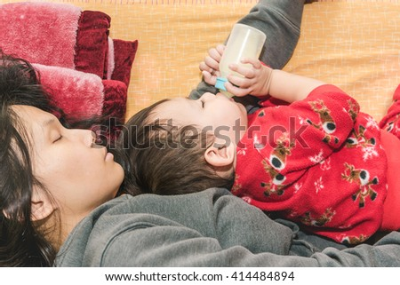 Asian mother holding baby in arm while  baby drinking milk from bottle while sleeping - stock photo