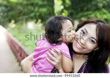 Asian mother holding daughter kissing her cheek and smiling.