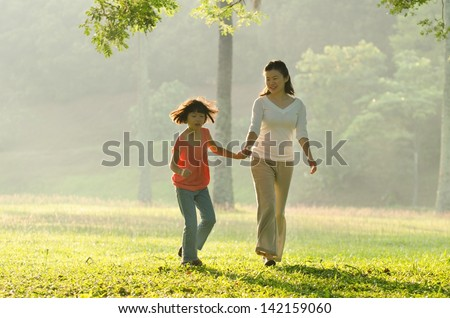 Asian mother holding her daughter's hand walking in the park - stock photo