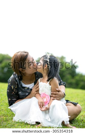 Asian mother is kissing his daughter in the park, Bangkok Thailand - stock photo