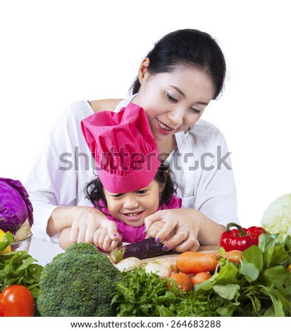 Asian mother is teaching her daughter to cut vegetable at home - stock photo